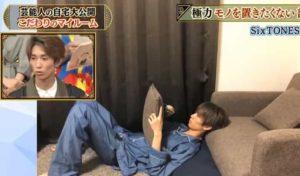 田中樹が自宅のクッションの毛玉を取りながらソファーにもたれる画像